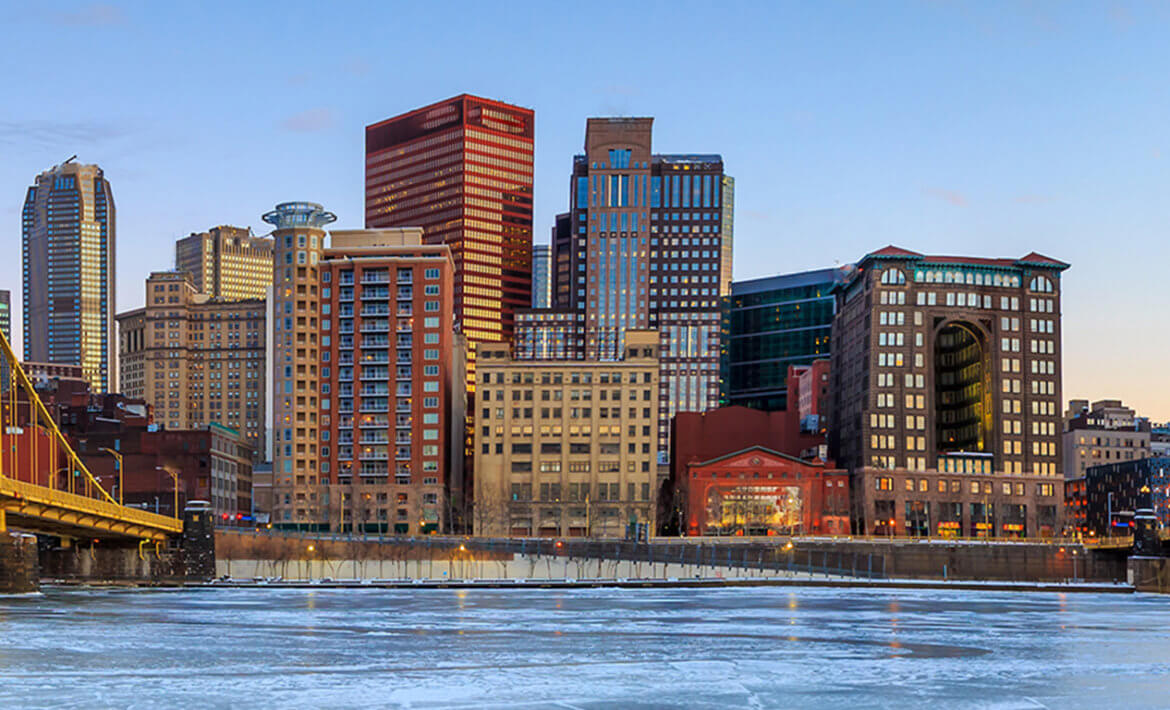 Skyline of Pittsburgh with water in the foreground.